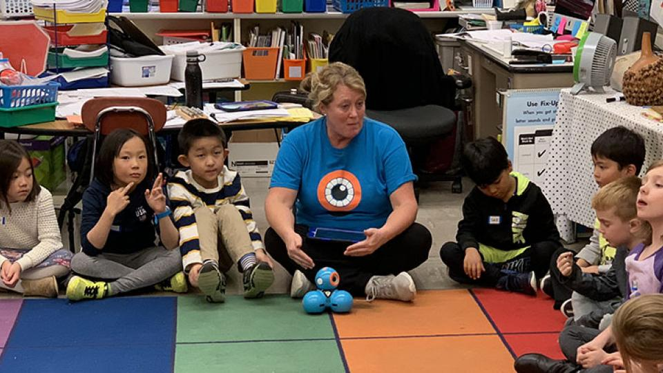 PCS teacher sitting with students in classroom during STEM club