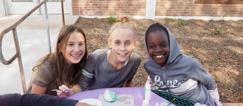 Student mentors greet our new students as they paint their own PEACE Rock.